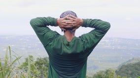 Ευτυχές άτομο που χαλαρώνει και που φαίνεται τοπίο κοιλάδων βουνών από την αιχμή Διακινούμενο άτομο που απολαμβάνει το όμορφο τοπ απόθεμα βίντεο