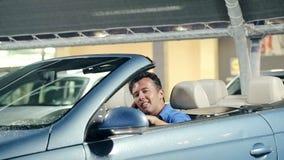Ευτυχές άτομο που χαμογελά και που μιλά στην έξυπνη τηλεφωνική συνεδρίαση πίσω από το τιμόνι φιλμ μικρού μήκους