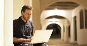 Ευτυχές άτομο που χρησιμοποιεί ένα lap-top στη νύχτα απόθεμα βίντεο