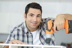 Ευτυχές άτομο που χρησιμοποιεί το τρυπάνι στο σπίτι στοκ φωτογραφίες
