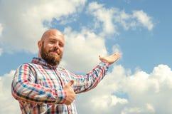 Ευτυχές άτριχο άτομο με τη γενειάδα που δείχνει το νεφελώδη όμορφο ουρανό στοκ φωτογραφίες