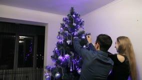 Ευτυχές έγκυο ζεύγος που διακοσμεί το χριστουγεννιάτικο δέντρο στο σπίτι τους απόθεμα βίντεο