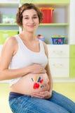 Ευτυχές έγκυο κορίτσι με τα γραμματόσημα φοινικών στην κοιλιά Στοκ φωτογραφίες με δικαίωμα ελεύθερης χρήσης