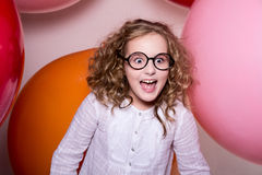 Ευτυχές έκπληκτο ευτυχές κορίτσι στο υπόβαθρο των μεγαλύτερων σφαιρών Στοκ εικόνες με δικαίωμα ελεύθερης χρήσης