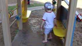Ευτυχές λίγο όμορφο αγόρι κάθεται στον πάγκο στην παιδική χαρά απόθεμα βίντεο