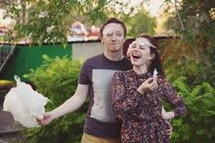 Ευτυχές αγαπώντας ζεύγος με την καραμέλα βαμβακιού που έχει τη διασκέδαση στο πάρκο Στοκ εικόνα με δικαίωμα ελεύθερης χρήσης