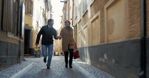 Ευτυχές αγαπώντας ζεύγος που τρέχει στην παλαιά οδό φιλμ μικρού μήκους
