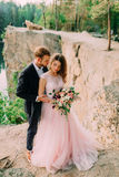 Ευτυχές αγκάλιασμα newlyweds Ο άνδρας στο σμόκιν και τη γυναίκα σε ένα ρόδινο γαμήλιο φόρεμα θέτει στη φύση Μια τελετή υπαίθρια Στοκ φωτογραφίες με δικαίωμα ελεύθερης χρήσης