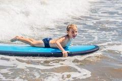 Ευτυχές αγοράκι - νέος γύρος surfer στην ιστιοσανίδα με τη διασκέδαση στη θάλασσα στοκ φωτογραφία με δικαίωμα ελεύθερης χρήσης