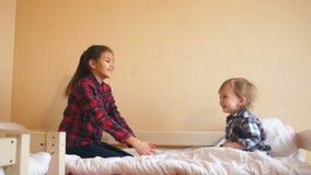 Ευτυχές αγοράκι που έχει τη διασκέδαση με την παλαιότερη αδελφή στο κρεβάτι απόθεμα βίντεο