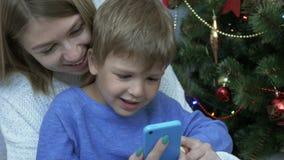 Ευτυχές αγόρι και η μητέρα του που εξετάζουν το έξυπνο τηλέφωνο κοντά στο χριστουγεννιάτικο δέντρο φιλμ μικρού μήκους