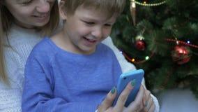 Ευτυχές αγόρι και η μητέρα του που εξετάζουν το έξυπνο τηλέφωνο κοντά στο χριστουγεννιάτικο δέντρο απόθεμα βίντεο