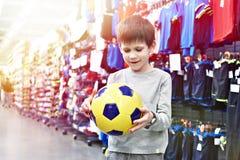Ευτυχές αγόρι με τη σφαίρα ποδοσφαίρου στο αθλητικό κατάστημα στοκ εικόνες με δικαίωμα ελεύθερης χρήσης