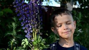 Ευτυχές αγόρι παιδιών με την ανθοδέσμη των άγριων λουλουδιών στα χέρια του που απολαμβάνεται μέχρι το καλοκαίρι χαριτωμένο αγόρι  φιλμ μικρού μήκους