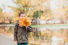 Ευτυχές αγόρι παιδιών που περπατά στο πάρκο Μέρη των κίτρινων φύλλων γύρω Το αγόρι φορά ένα καφετί σακάκι στοκ εικόνες με δικαίωμα ελεύθερης χρήσης