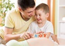Ευτυχές αγόρι παιδιών και το παιχνίδι πατέρων του με τα παιχνίδια επάνω στοκ εικόνες