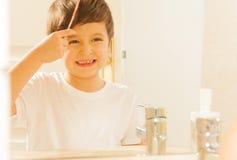 Ευτυχές αγόρι παιδιών που κτενίζει την τρίχα του το πρωί Στοκ Εικόνες