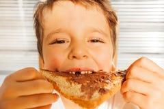 Ευτυχές αγόρι παιδιών που τρώει τη φρυγανιά με τη σοκολάτα που διαδίδεται Στοκ Φωτογραφίες