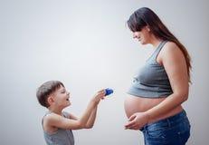 Ευτυχές αγόρι που δίνει στη έγκυο γυναίκα ένα δώρο στοκ εικόνα