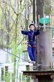 Ευτυχές αγόρι που αναρριχείται στο πάρκο περιπέτειας Στοκ Εικόνες