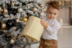 Ευτυχές αγόρι που βάζει στο πάτωμα με τα δώρα Χριστουγέννων στο διακοσμημένο δωμάτιο στοκ φωτογραφία