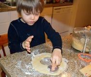Ευτυχές αγόρι που κατασκευάζει τα μπισκότα καρδιών Στοκ Φωτογραφία