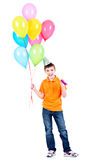 Ευτυχές αγόρι που κρατά τα ζωηρόχρωμα μπαλόνια Στοκ Εικόνες