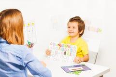 Ευτυχές αγόρι που κρατά το σχέδιο με τις χρωματισμένες μορφές Στοκ Εικόνες