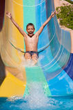 Ευτυχές αγόρι που κυλά με τα waterslides Στοκ εικόνα με δικαίωμα ελεύθερης χρήσης