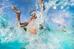 Ευτυχές αγόρι που παίζει και που καταβρέχει στην πισίνα Στοκ Φωτογραφία