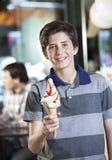 Ευτυχές αγόρι που παρουσιάζει παγωτό βανίλιας στην αίθουσα στοκ εικόνα με δικαίωμα ελεύθερης χρήσης