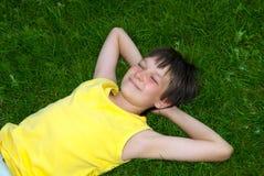 Ευτυχές αγόρι που στηρίζεται στη χλόη στοκ εικόνα
