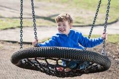 Ευτυχές αγόρι που ταλαντεύεται σε μια μεγάλη στρογγυλή ταλάντευση Στοκ φωτογραφία με δικαίωμα ελεύθερης χρήσης