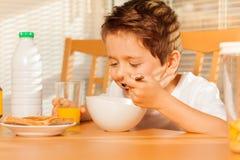 Ευτυχές αγόρι που τρώει τα δημητριακά και που πίνει το φρέσκο χυμό Στοκ Εικόνες