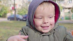 Ευτυχές αγόρι σε εύθυμος-πηγαίνω-στρογγυλό στο πάρκο ιπποδρόμιο φιλμ μικρού μήκους