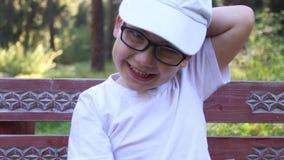 Ευτυχές αγόρι στα γυαλιά και τα γέλια ΚΑΠ φιλμ μικρού μήκους