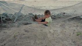 Ευτυχές αγόρι στην αιώρα στην παραλία απόθεμα βίντεο