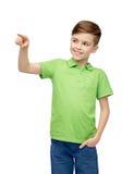 Ευτυχές αγόρι στην πράσινη μπλούζα πόλο που δείχνει το δάχτυλο επάνω στοκ φωτογραφία με δικαίωμα ελεύθερης χρήσης
