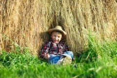 Ευτυχές αγόρι στη συνεδρίαση καπέλων αχύρου στη θυμωνιά χόρτου Στοκ εικόνες με δικαίωμα ελεύθερης χρήσης