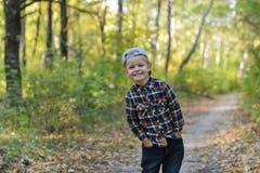Ευτυχές αγόρι στο δάσος φθινοπώρου Στοκ φωτογραφία με δικαίωμα ελεύθερης χρήσης