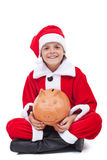 Ευτυχές αγόρι στο κοστούμι santa με τη piggy τράπεζα Στοκ Φωτογραφία