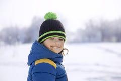 Ευτυχές αγόρι στο παιχνίδι χιονιού και την ηλιόλουστη ημέρα χαμόγελου Στοκ Φωτογραφία