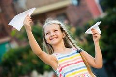 Ευτυχές αεροπλάνο εγγράφου κοριτσιών παίζοντας Στοκ Εικόνα