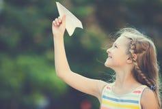 Ευτυχές αεροπλάνο εγγράφου κοριτσιών παίζοντας Στοκ Εικόνες