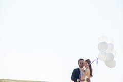 Ευτυχές ακριβώς παντρεμένο ζευγάρι με τα μπαλόνια διαθέσιμα Στοκ Εικόνες