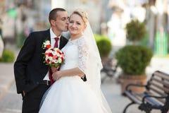 Ευτυχές ακριβώς παντρεμένο ζευγάρι σε ένα υπόβαθρο του όμορφου archi Στοκ Φωτογραφία