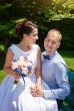 Ευτυχές ακριβώς παντρεμένο νέο γαμήλιο ζευγάρι που έχει τη διασκέδαση στο πάρκο Νύφη και νεόνυμφος μαζί, θέμα αγάπης και γάμου Στοκ Φωτογραφία