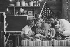 Ευτυχές αμερικανικό οικογενειακό παιχνίδι με τον κατασκευαστή στο σπίτι μητέρα και πατέρας που βοηθούν να χτίσει την κατασκευή με Στοκ Εικόνες