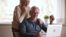 Ευτυχές ανώτερο αγκάλιασμα ομιλίας γέλιου ζευγών χρησιμοποιώντας το lap-top από κοινού απόθεμα βίντεο