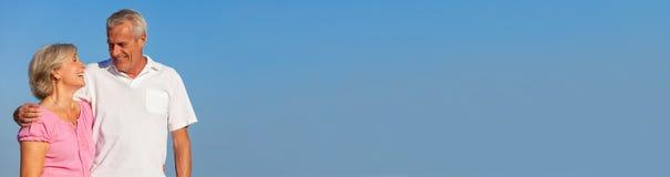 Ευτυχές ανώτερο αγκάλιασμα περπατήματος ζεύγους στο πανόραμα μπλε ουρανού στοκ εικόνες